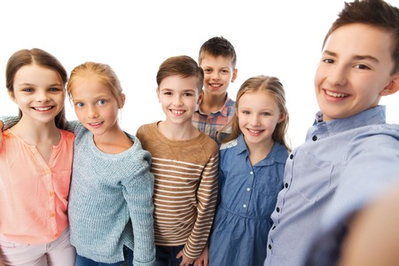 pre adolescent boy: childhood, friendship, technology and people concept - happy children talking selfie Stock Photo