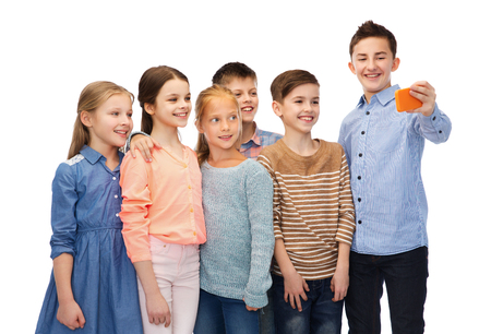 pre teen boy: childhood, friendship, technology and people concept - happy children talking selfie by smartphone Stock Photo