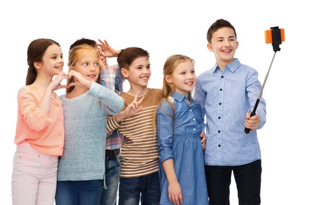 pre adolescent boy: childhood, friendship, technology and people concept - happy children talking picture by smartphone on selfie stick
