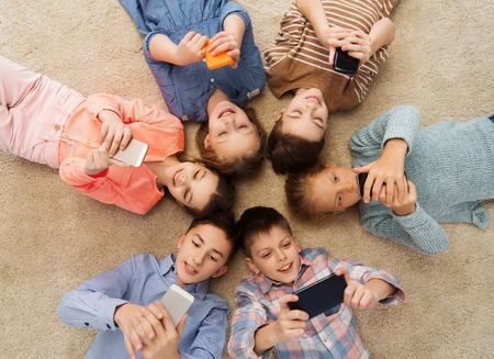 friends together: childhood, fashion, friendship and people concept - happy smiling children lying on floor in circle