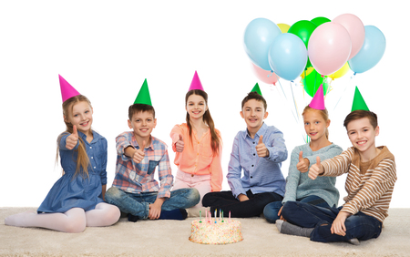 pre approval: childhood, holidays, friendship and people concept - happy smiling children in party hats with birthday cake and balloons showing thumbs up