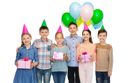 pre teen boys: childhood, holidays, friendship and people concept - happy smiling children in party hats with gifts and balloons on birthday Stock Photo