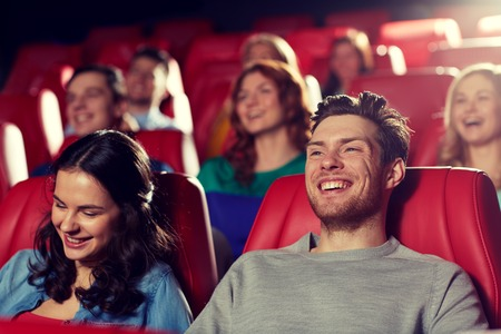 at the theater: cinema, entertainment and people concept - happy friends watching comedy movie in theater