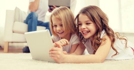 ni�os jugando videojuegos: familia, los ni�os, la tecnolog�a y el concepto de casa - hermana sonriente con la tableta inform�tica PC y los padres en la parte posterior con el ordenador port�til