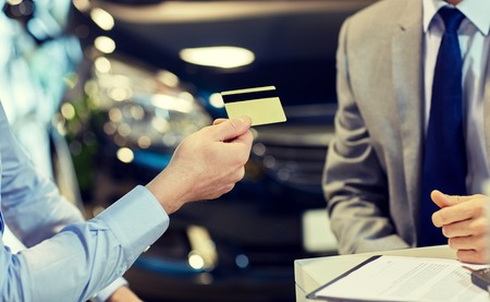 credit card purchase: auto business, sale and people concept - close up of customer giving credit card to car dealer in auto show or salon