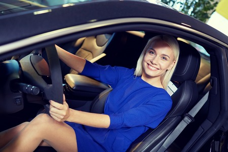 driving a car: auto business, car sale, consumerism , transportation and people concept - happy woman sitting in or driving car