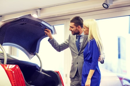 car trunk: auto business, car sale, technology and people concept - happy couple with car dealer in auto show or salon