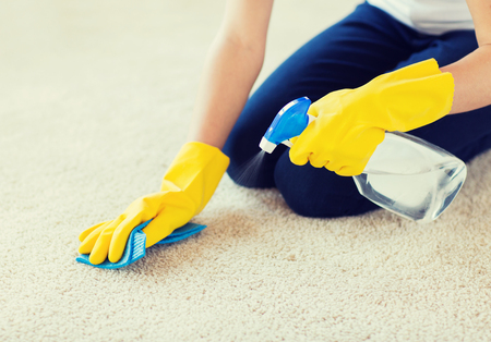 carpet: people, housework and housekeeping concept - close up of woman in rubber gloves with cloth and detergent spray cleaning carpet at home