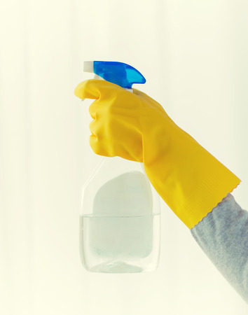 cleanser: people, housework and housekeeping concept - close up of hand with cleanser spraying home