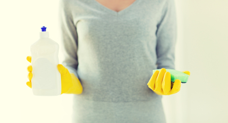 cleanser: people, housework, washing-up and housekeeping concept - close up of woman holding sponge and cleanser bottle at home