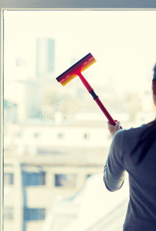 cleaning window: people, housework and housekeeping concept -close up of woman cleaning window with sponge mop