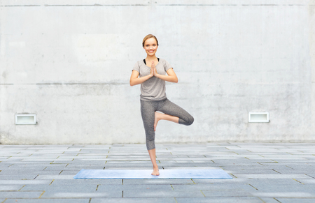 woman posture: fitness, sport, people and healthy lifestyle concept - woman making yoga in tree pose on mat over urban street background