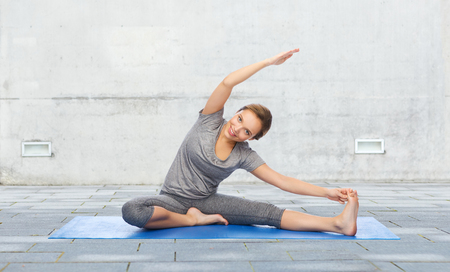 to bend: fitness, sport, people and healthy lifestyle concept - happy woman making yoga and stretching on mat over urban street background Stock Photo