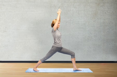 warrior pose: fitness, sport, people and healthy lifestyle concept - woman making yoga warrior pose on mat over gym room background