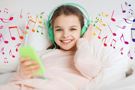 personas, niños y concepto de la tecnología - niña feliz despierto con el teléfono inteligente y los auriculares en la cama escuchando música en casa sobre las notas musicales sonriendo