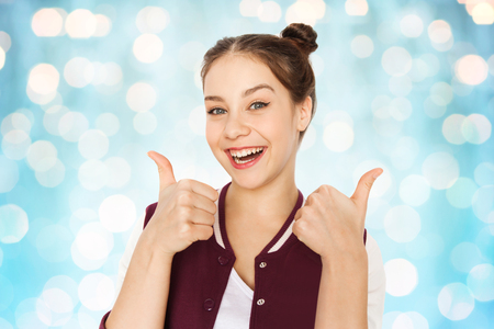 beautiful teen girl: people and teens concept - happy smiling pretty teenage girl showing thumbs up over blue holidays lights background