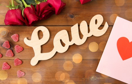 attentions: romance, valentines day and holidays concept - close up of word love, gift box, red roses and greeting card with heart-shaped candies on wood Stock Photo