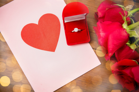 attentions: love, proposal, valentines day and holidays concept - close up of gift box with diamond engagement ring, red roses and greeting card on wood Stock Photo