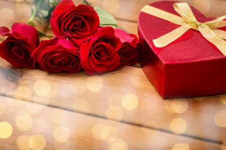 courtship: love, date, romance, valentines day and holidays concept - close up of heart shaped gift box and red roses on wooden table