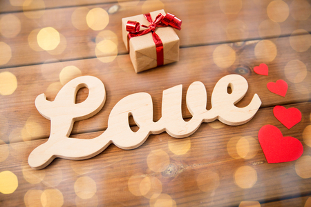 flirtation: love, date, romance, valentines day and holidays concept - close up of word love with gift box and red hearts on wood