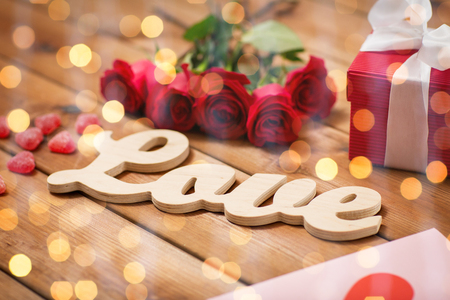 uprzejmości: romance, valentines day and holidays concept - close up of word love, gift box, red roses and greeting card with heart-shaped candies on wood over lights background