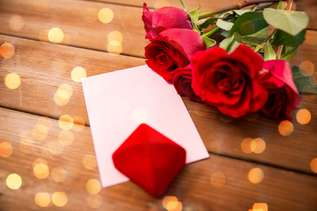 attentions: love, romance, valentines day and holidays concept - close up of gift box, red roses and greeting card with heart on wood over lights background Stock Photo