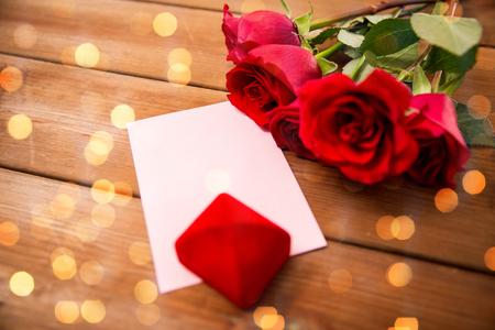 uprzejmości: miłość, romans, Walentynki i święta pojęcie - zamknąć pudełko, czerwonych róż i kartkę z życzeniami z serca na tle drewna na światłach