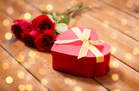 uprzejmości: love, date, romance, valentines day and holidays concept - close up of heart shaped gift box and red roses on wooden table over lights background