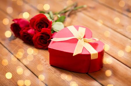 uprzejmości: miłość, data, romans, Walentynki i święta pojęcie - zamknąć w kształcie serca pudełko i czerwonych róż na drewnianym stole na tle światła