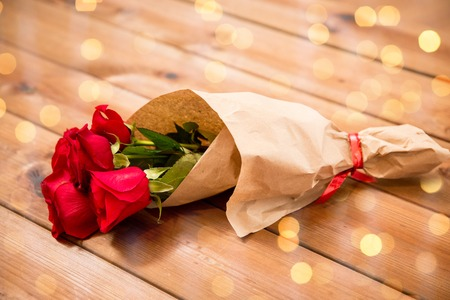 attentions: love, date, flowers, valentines day and holidays concept - close up of red roses bunch wrapped into brown paper on wooden table over lights background
