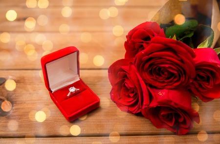 amor, oferta, el día de San Valentín y concepto de vacaciones - cerca de la caja de regalo con el anillo de compromiso de diamantes y rosas rojas en la madera sobre fondo de las luces