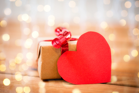 attentions: love, date, romance, valentines day and holidays concept - close up of gift box and blank red heart-shaped note on wood over lights background