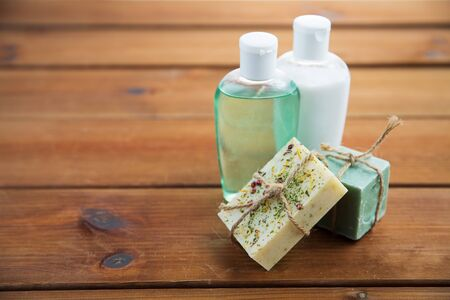 beauty, spa, body care, bath and natural cosmetics concept - close up of handmade soap bars and lotion bottles on wooden table