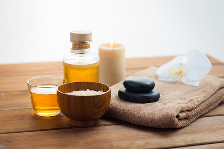 美容、スパ、ボディケア、自然化粧品、コンセプト - クローズ アップ マッサージ オイルとバスタオルを木製のテーブルの上でピンクの塩