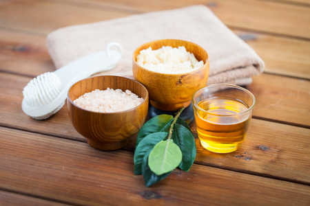 bath salt: beauty, spa, body care, natural cosmetics and bath concept - close up of himalayan pink salt and body scrub with brush on wooden table
