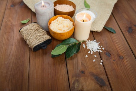 natural therapy: beauty, spa, therapy, natural cosmetics and wellness concept - close up of body scrub with  himalayan pink salt and candles on wood Stock Photo