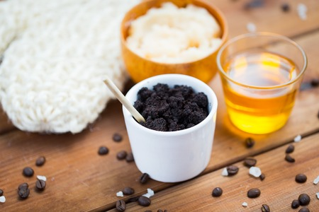 ground: beauty, spa, body care, bath and natural cosmetics concept - close up of coffee scrub in cup and honey on wooden table