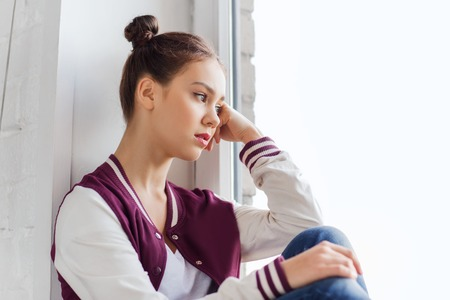 Menschen, Emotion und Jugendliche Konzept - traurig unglücklich hübsche Teenager-Mädchen auf der Fensterbank sitzen