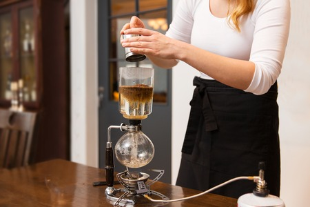 siphon: equipment, coffee shop, people and technology concept - close up of woman with pot pouring ground coffee to siphon coffeemaker at cafe bar or restaurant kitchen