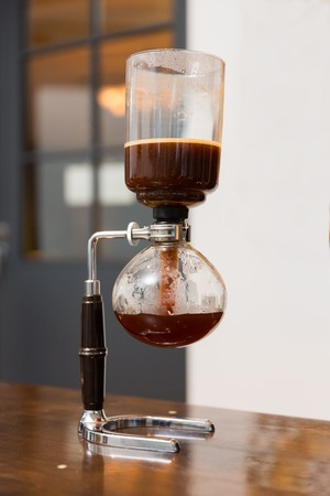siphon: equipment, coffee shop and technology concept - close up of siphon vacuum coffee maker at shop