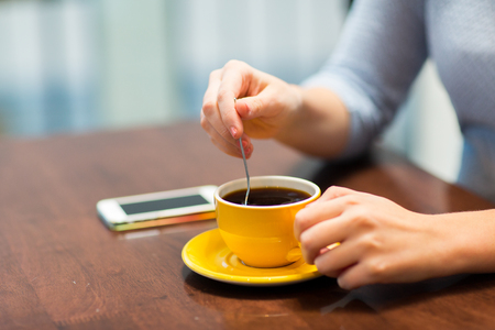 stirring: drinks, people, technology and lifestyle concept - close up of young woman with smartphone drinking coffee at cafe