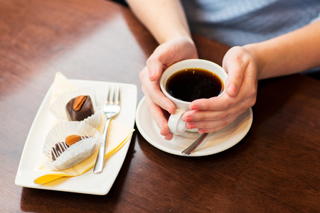 handmade: drinks, people and lifestyle concept - close up of woman hands holding cup with hot black coffee and dessert