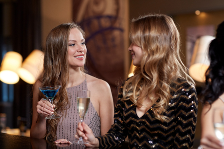 celebración, amigos, despedida de soltera y concepto de vacaciones - mujeres felices que beben el champán y cócteles en el club nocturno Foto de archivo