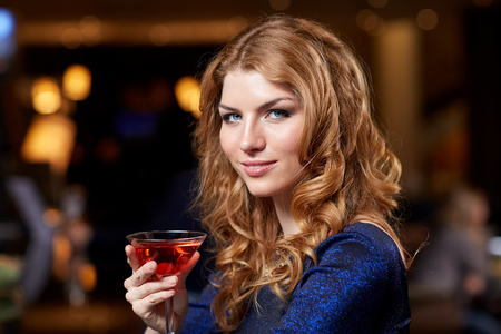 cocktail bar: people, party, nightlife, drink and holidays concept - glamorous woman with cocktail at night club or bar