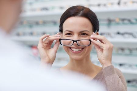 mucha gente: cuidado de la salud, las personas, la vista y la visión concepto - mujer feliz elegir y que muestra las gafas de óptica en la tienda de óptica