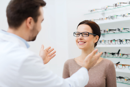 optical: health care, people, eyesight and vision concept - optician and woman in glasses at optics store Stock Photo