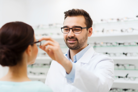 specs: health care, people, eyesight and vision concept - optician putting glasses to woman at optics store Stock Photo