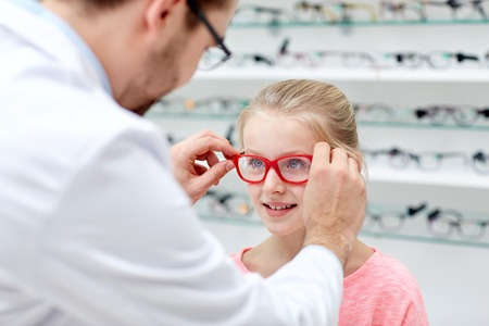 choosing: health care, people, eyesight and vision concept - optician putting glasses to little girl eyes at optics store Stock Photo