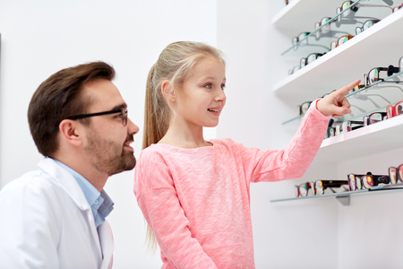 kids wear: health care, people, eyesight and vision concept - optician and smiling girl choosing glasses at optics store Stock Photo