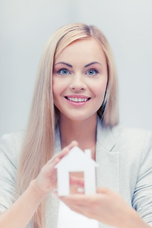 costruction: picture of young woman holding white paper house